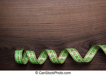 green measuring tape over brown wooden background - green...