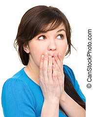 Woman is covering her mouth in astonishment - Young woman is...