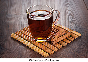 teacup with hot tea and cinnamon sticks on the table