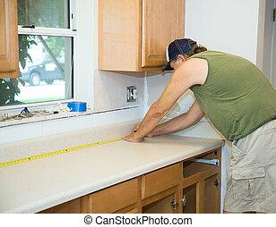 Carpenter Measures Counter Top - Carpenter measuring...