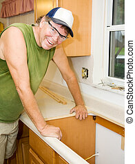 Contractor Remodels Kitchen - Friendly contractor leans on a...