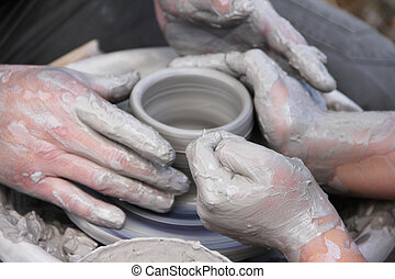 Msking of ceramic pot - A potters hands guiding a child...