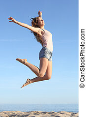 Beautiful woman jumping happy on the beach with a blue sky...