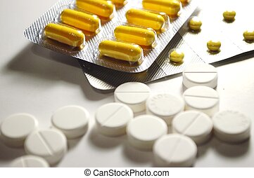 White and yellow pills - Assorted pills and yellow capsules...