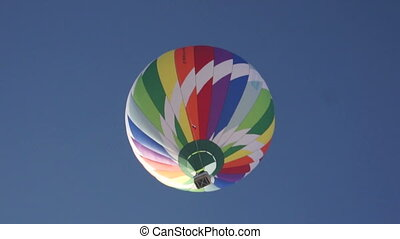 Colorful hot air balloon rises in sky