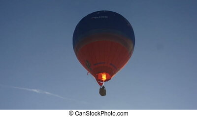 Blue and red hot air balloon rises in sky