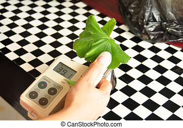 Chlorophyll Meter - hand with chlorophyll meter instrument...