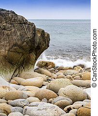 Water worn ancient rocks detail on secluded beach