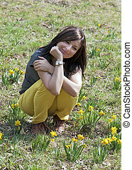 Young woman with daffodils - Young woman squats between...