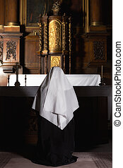 Prayer at the altar - Nun praying at the altar of a medieval...