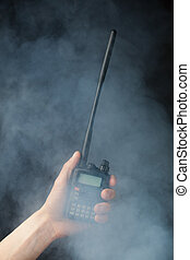 professional walkie-talkie radio in hand in smoke