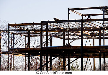 Construction workers working on a steel frame building