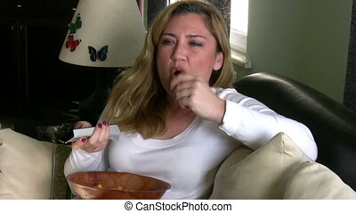 Woman watching tv and eating chips