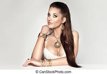 Beautiful brunette woman wearing a lot of jewelry.