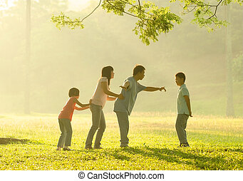 happy asian family playing having quality time at outdoor green  park