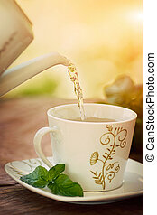 Cup of tea. Pouring hot water for herbal mint tea