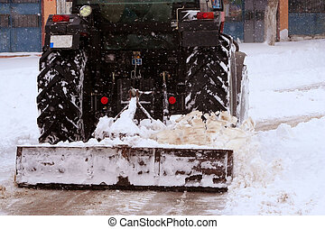 Cleaning street from snow by tractor