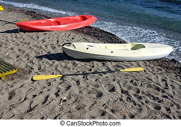 Two canoes are on the beach