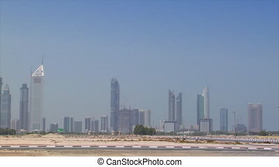 small car cross Dubai skyline pan burj emirates