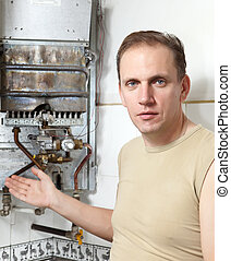 The man  thinks of repair of a gas water heater