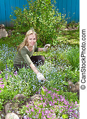 Young pretty woman looks after behind plants in the garden...