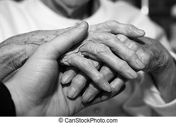 Hand On Hand - Young hand holding seniors hand