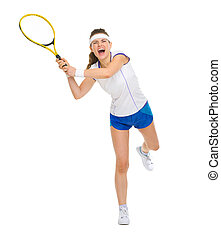 Full length portrait of female tennis player hitting ball