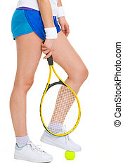 Closeup on female tennis player standing with one foot on ball