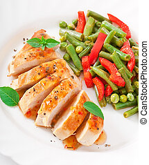 Chicken breast with vegetables and sauce decorated with...