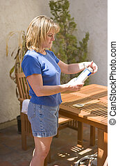 Woman reading instructions to seal a table - Woman preparing...