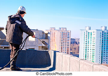 Roofer worker installing roofing felt by means of gas...