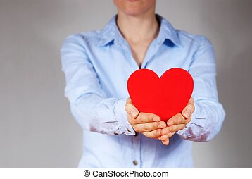 person holding a heart - a person in blue shirt holding a...