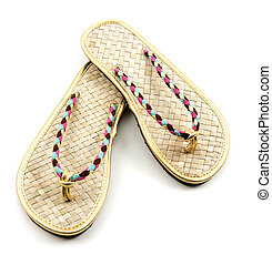 Raffia golden braided flip flop sandals isolated on white...