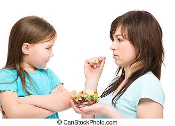 Mother is trying to feed her daughter with fruit salad,...