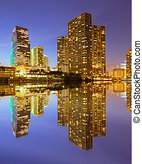 City of Miami Florida, night skyline. Cityscape of residential and business buildings lit by bright lights after sunset with reflections