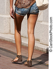 legs of a young girl in blue jeans shorts