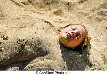 young girl is covered by sand at the beach