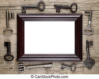 Photo frame and vintage keys on wooden background