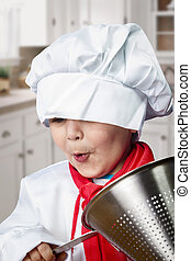 Funny boy dressed in chef with pasta drainer