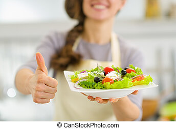 Closeup on woman showing fresh salad and thumbs up