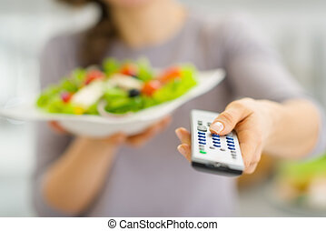 Closeup on tv remote control and fresh salad in hand of...