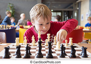 Young chess player at a tournament - Young child making a...