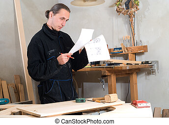 Carpenter - Young carpenter in his workshop with planning in...