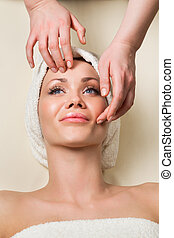 Beautiful young woman receiving facial massage - Human hands...