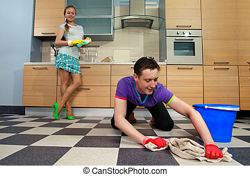 Man cleaning floor - Young man cleaning floor and looking at...