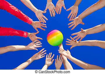volley ball - Several hands reaching out together in a...