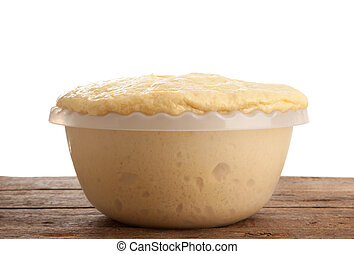 Rising Yeast Dough in bowl on wooden table