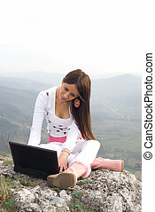 Wireless communication - Young woman using his laptop,...