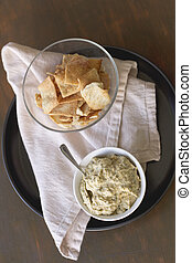 Artichoke Hummus - Artichoke hummus with pita chips on a...