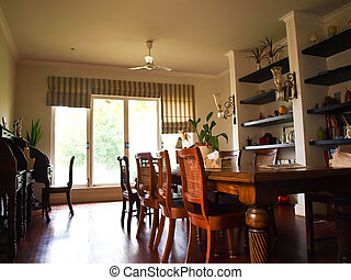 Dining room interior with classic brown furniture and natural light.